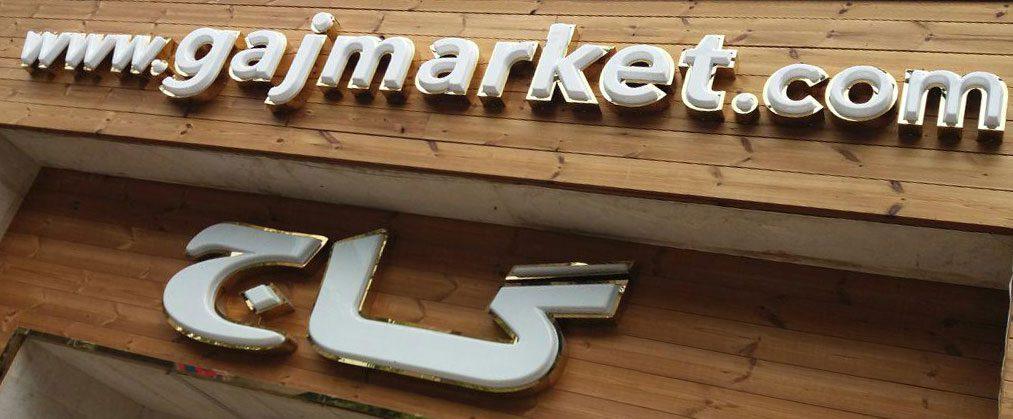 تابلوی چوب ترموود و حروف وکیوم برجسته با رینگ استیل طلایی گاج شعبه ظفر